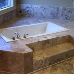 white bathtub surrounded with beige granite