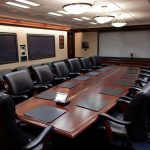 brown conference table surrounded by black office chairs