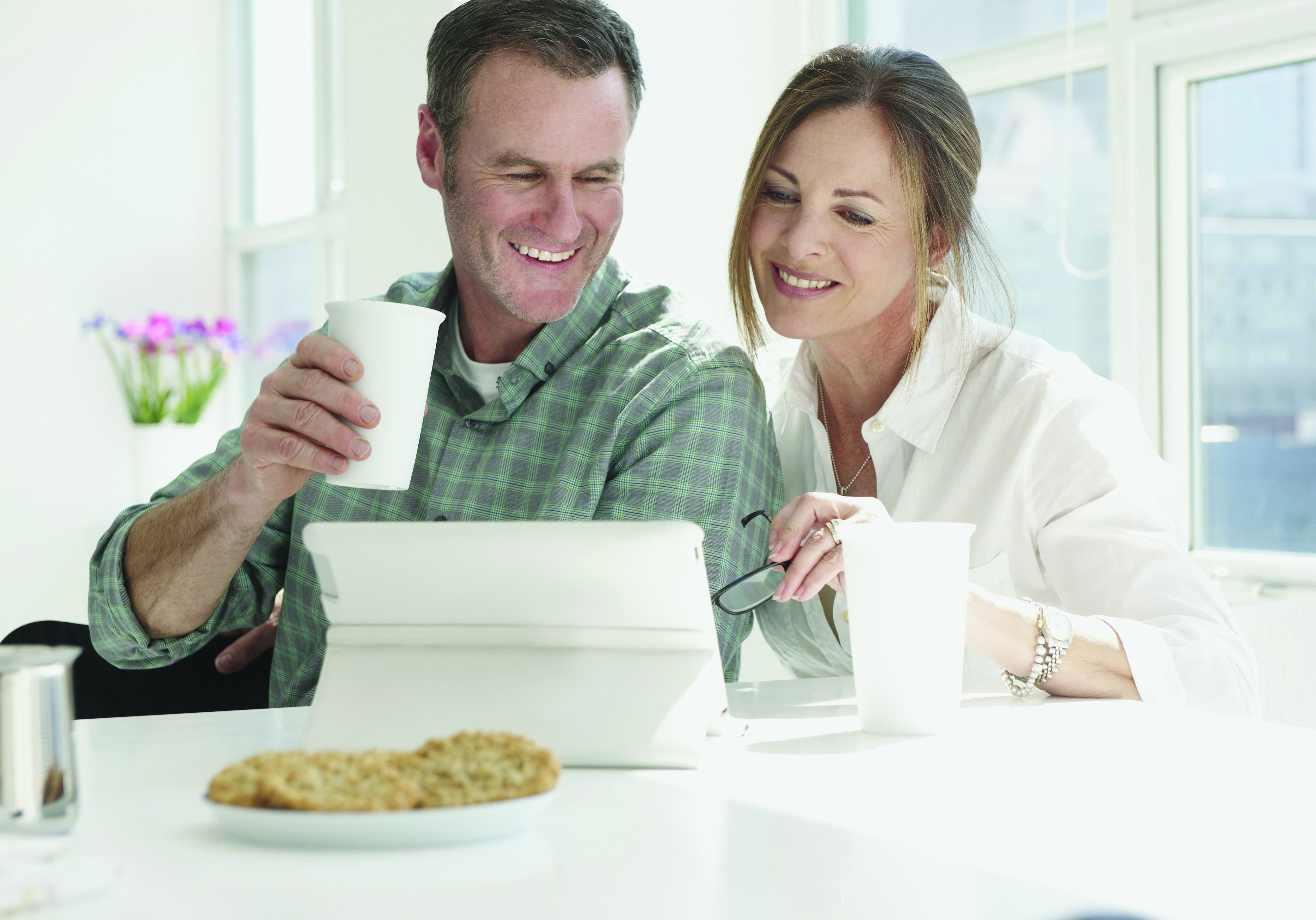 couple drinking coffee and looking at tablet computer