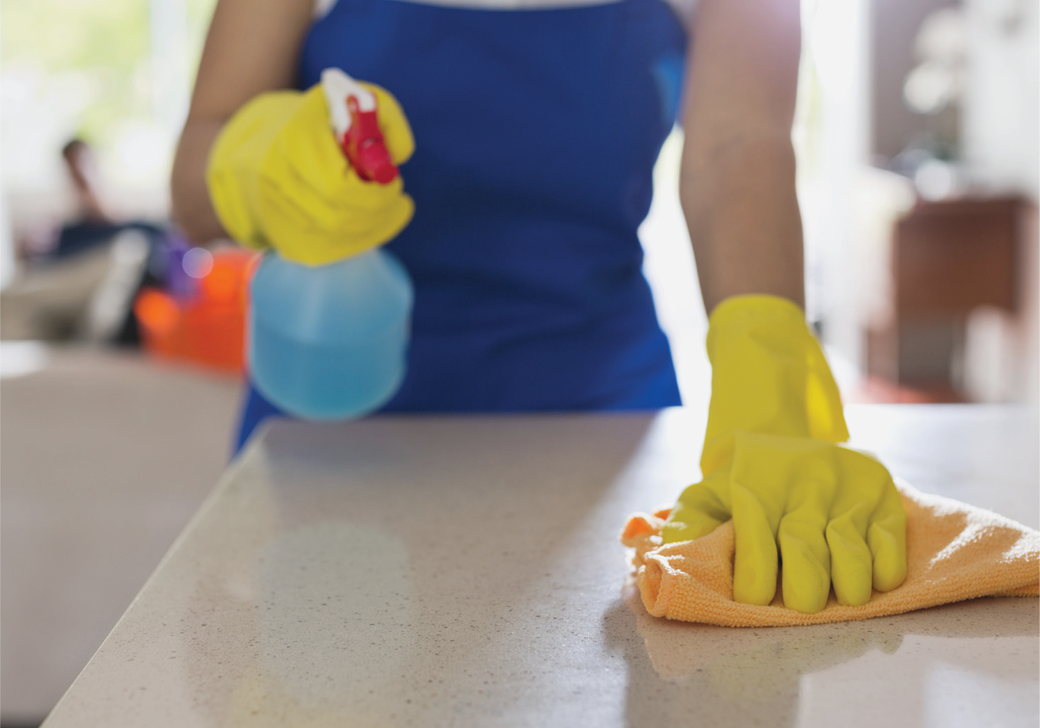 person wearing gloves and cleaning counter